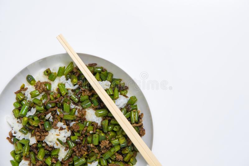 Bowl of minced beef with round beans and rice, with chopsticks on white background stock image