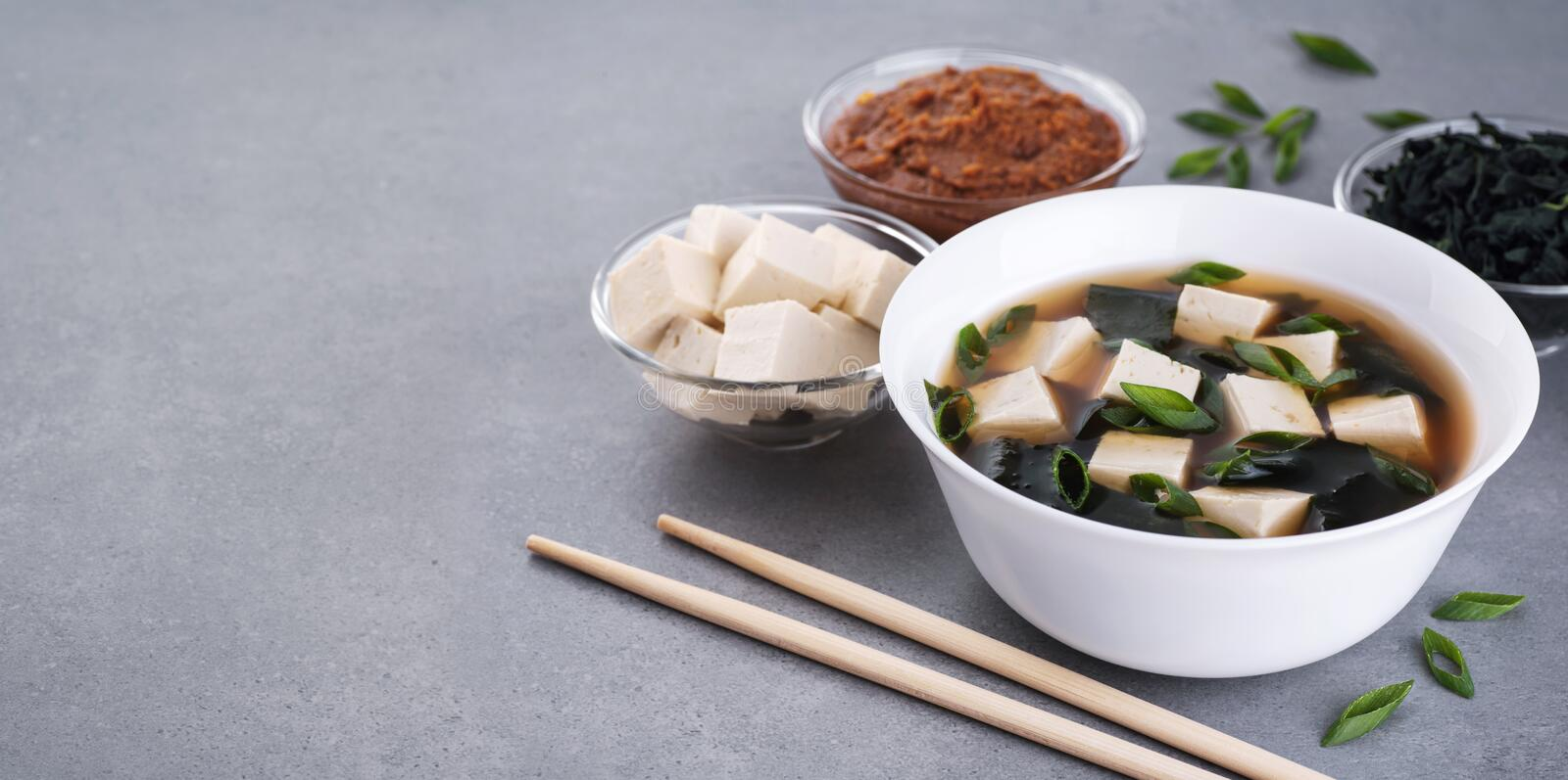 Bowl with miso soup, wakame seaweed, miso pasta, tofu and chopsticks on a gray background stock photography