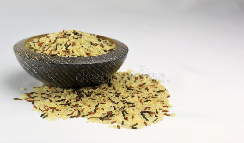 A mix of three grains of rice, Basmati, Wild and Brown or Red rice. A bowl of mixed rice on a white background. Basmati, Wild and red or brown rice grains stock images