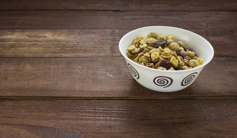 Bowl of muesli with dried fruits on wooden table stock photo