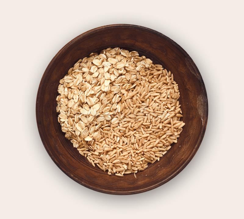 Bowl of oat flakes and grains isolated on white stock images