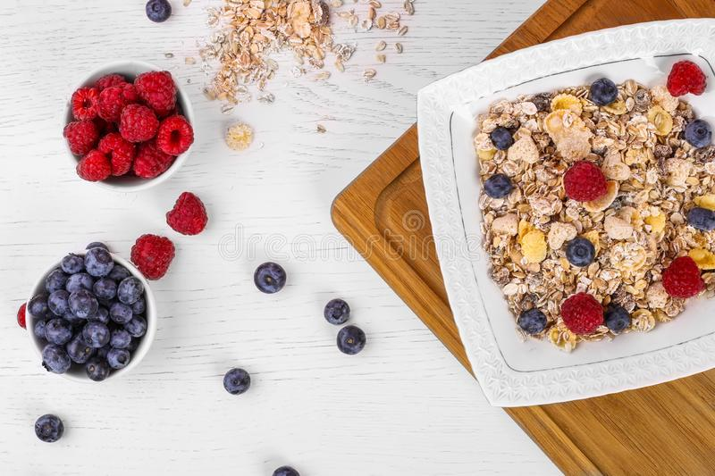 Bowl of oat granola, muesli with fresh raspberries, blueberries on white wooden board for healthy breakfast. top view royalty free stock photography