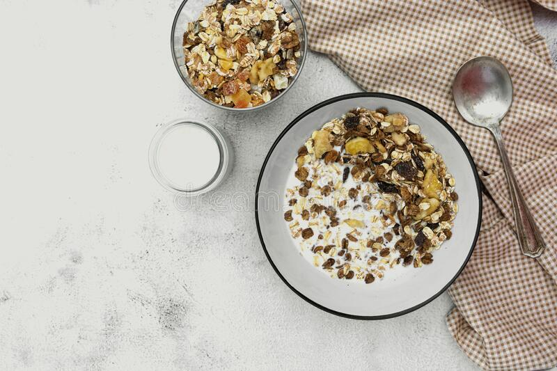 Bowl of oatmeal cereal. Whole oats, granola with dried fruit and blueberry, milk and honey. Healthy food breakfast. Copy space royalty free stock images