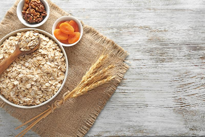 Bowl with oatmeal flakes, dried apricots and nuts on wooden table stock photo