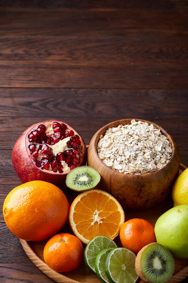 Bowl with oatmeal flakes served with fruits on wooden tray over rustic background, flat lay, selective focus royalty free stock photo