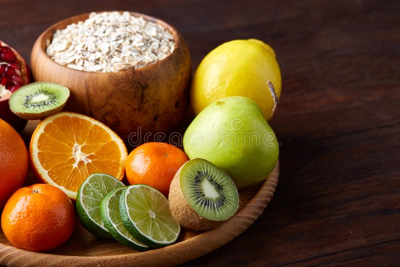 Bowl with oatmeal flakes served with fruits on wooden tray over rustic background, flat lay, selective focus royalty free stock images