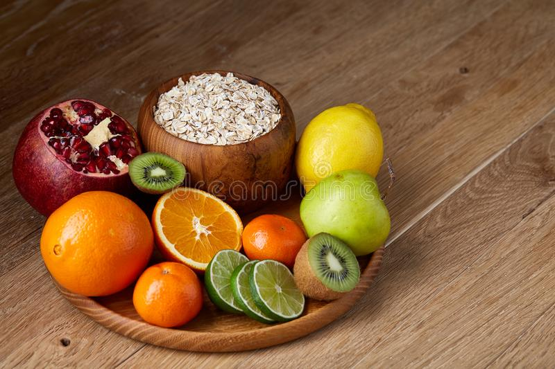 Bowl with oatmeal flakes served with fruits on wooden tray over rustic background, flat lay, selective focus stock photography