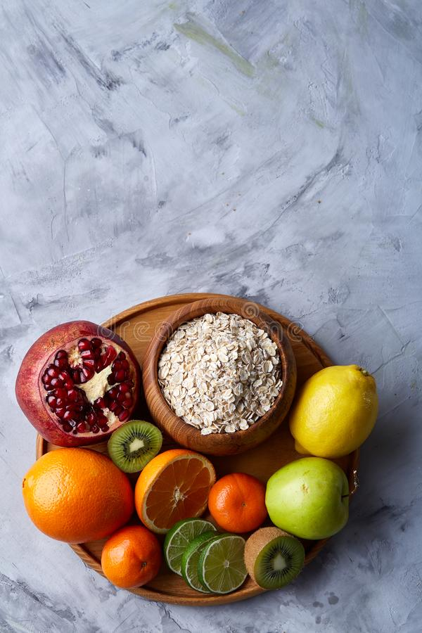 Bowl with oatmeal flakes served with fruits on wooden tray over white background, flat lay, selective focus royalty free stock image
