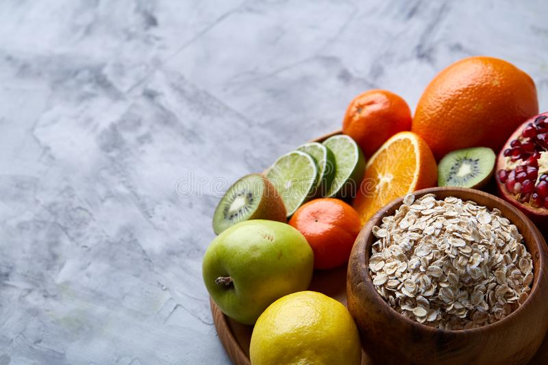 Bowl with oatmeal flakes served with fruits on wooden tray over white background, flat lay, selective focus royalty free stock images