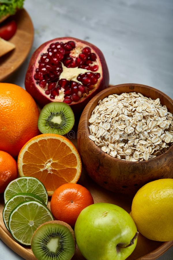 Bowl with oatmeal flakes served with fruits on wooden tray white background, flat lay, selective focus royalty free stock image