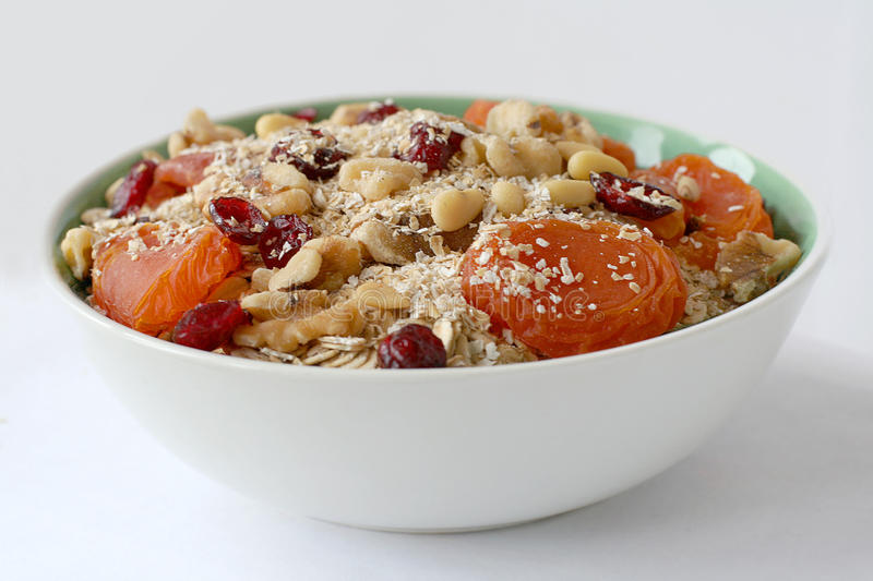 Bowl of oatmeal with nuts and fruits stock image