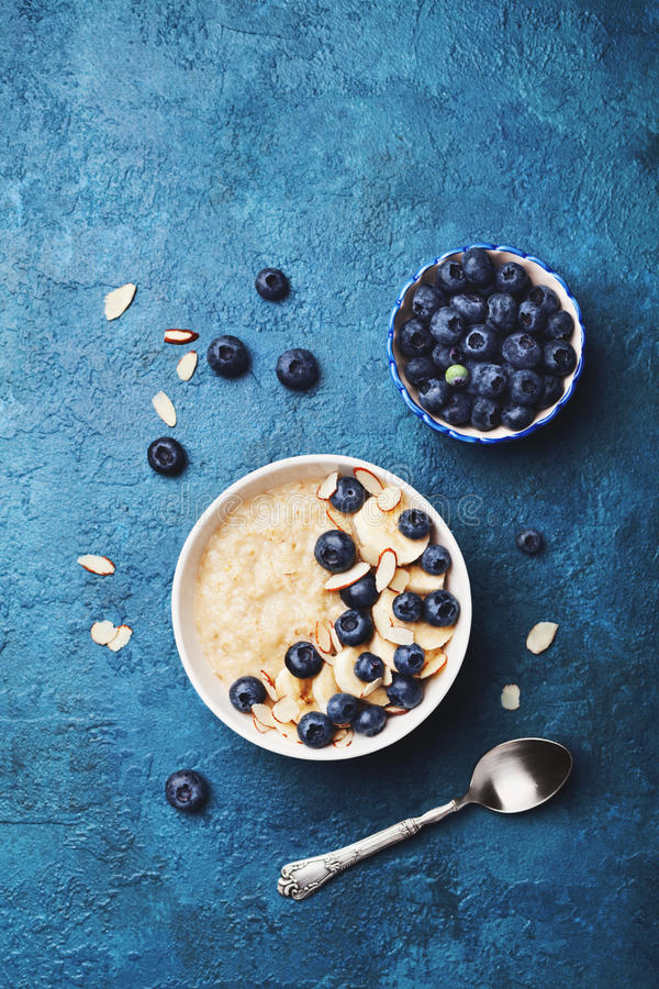 Bowl of oatmeal porridge with banana and blueberry on vintage table top view in flat lay style. Hot breakfast and diet food. stock photography