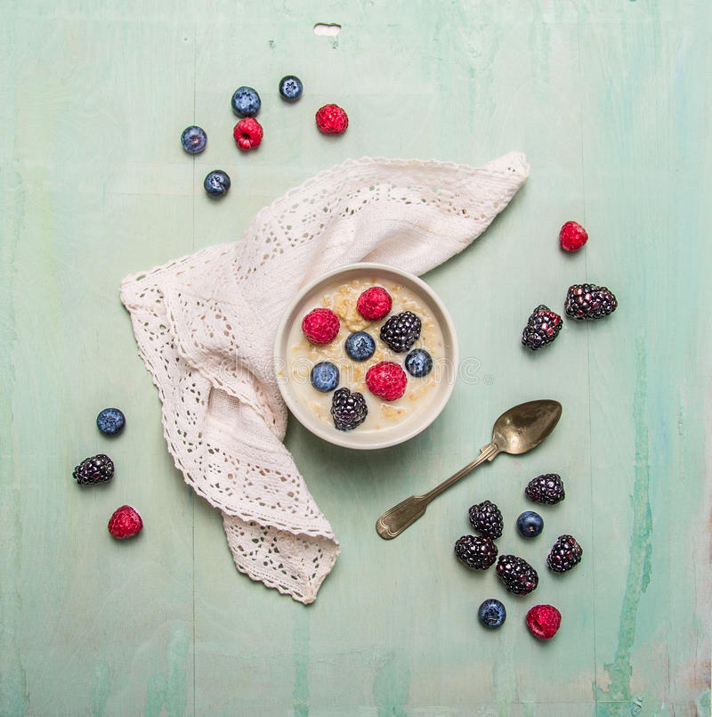 Bowl of oatmeal porridge with berries on blue rustic wooden background royalty free stock photos