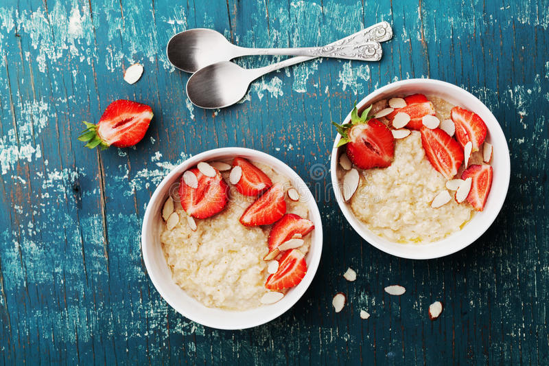 Bowl of oatmeal porridge with strawberry and almond flakes on rustic teal table top view in flat lay style. Healthy breakfast. stock photography