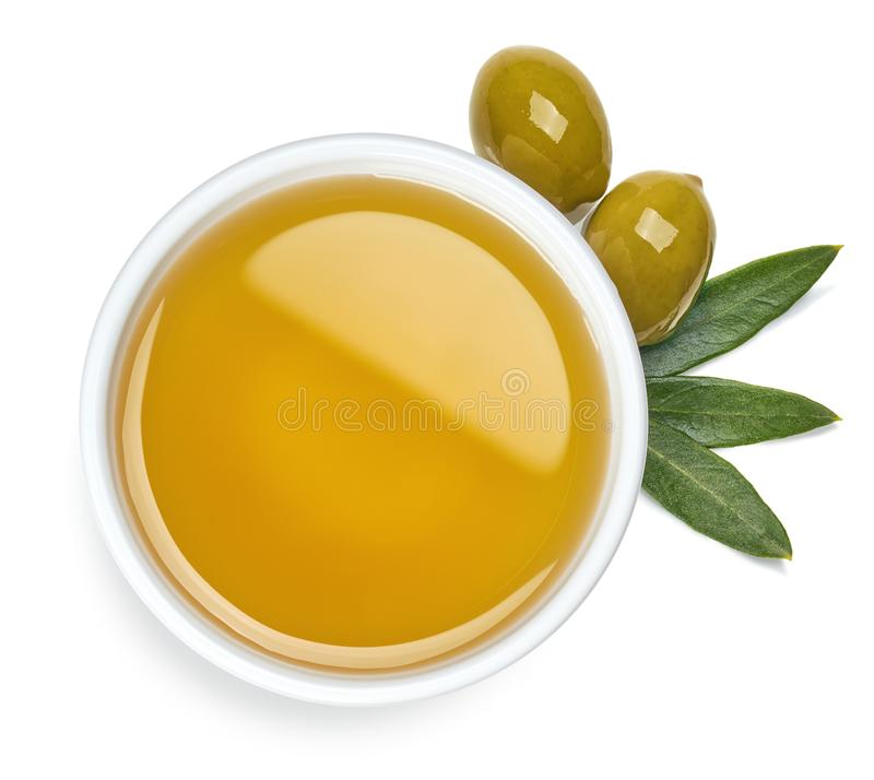 Bowl of olive oil and green olives with leaves royalty free stock photography