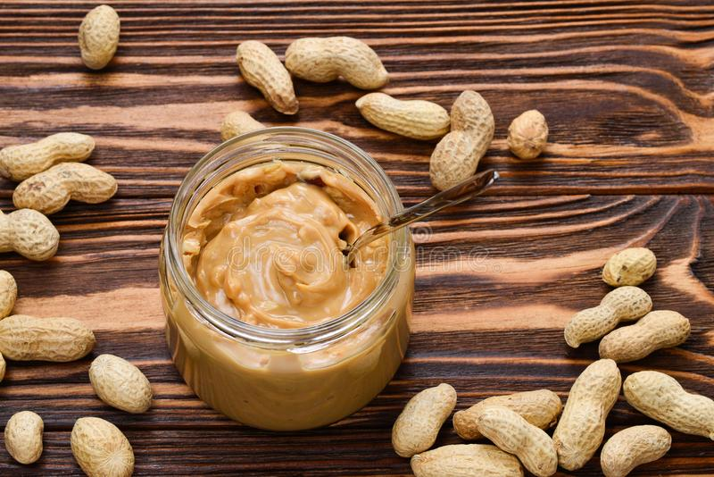 Bowl of peanut butter and peanuts on wooden background from stock images