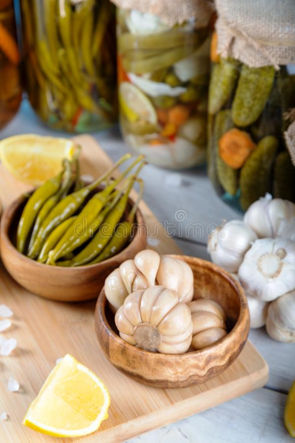 Bowl of pickled garlics and green peppers stock image