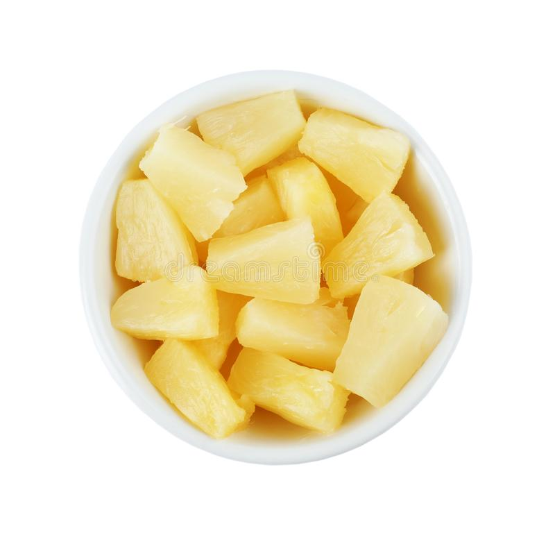 Bowl with pieces of delicious sweet canned pineapple on background, top view royalty free stock photography