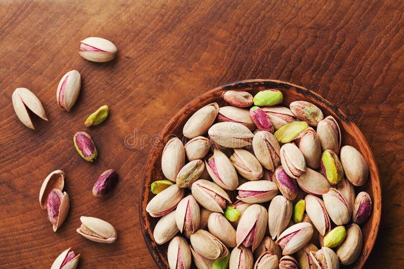 Bowl of pistachio nuts on wooden rustic table top view. Healthy food and snack. royalty free stock photos