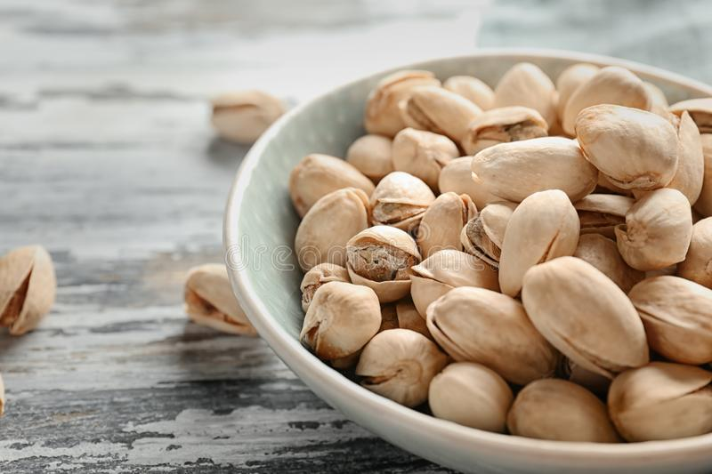 Bowl with pistachio nuts on wooden table, closeup royalty free stock image