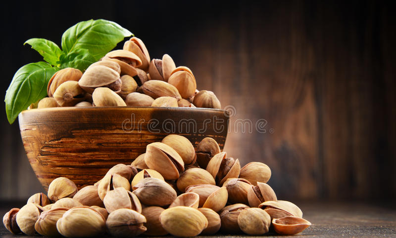 Bowl with pistachio on wooden table. Delicacies royalty free stock photos