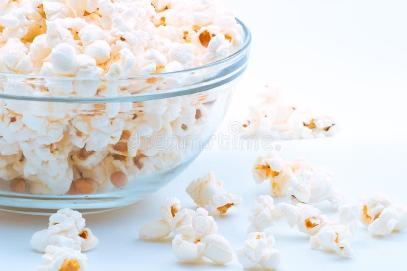 Bowl of popcorn. Closeup of glass bowl of popcorn with few peaces throw around stock photos