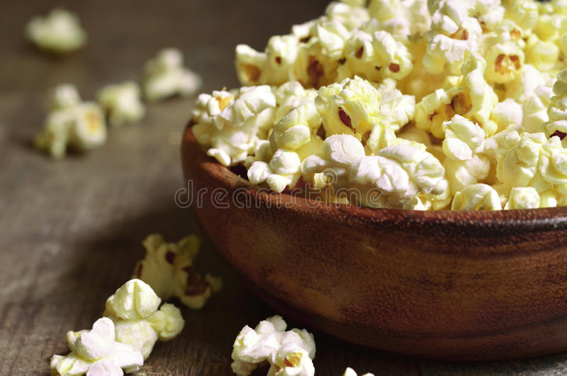 A bowl of popcorn . A bowl of popcorn on a wooden table royalty free stock photos