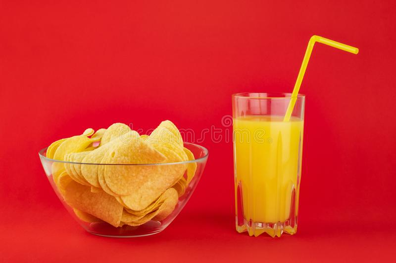 Bowl of potato chips and glass of orange drink in bright red background. Minimalistic image of attention grabbing snacks and royalty free stock photo