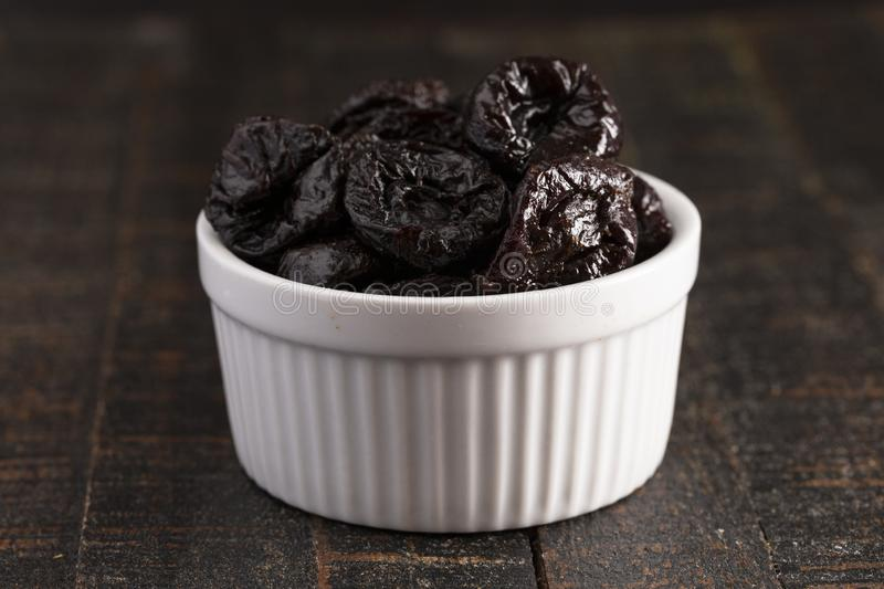 Bowl of Prunes on a Rustic Wooden Table royalty free stock photos