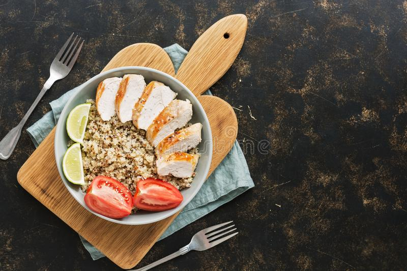 Bowl with quinoa and chicken fillet on a dark rustic background. Top view, flat lay. royalty free stock photos