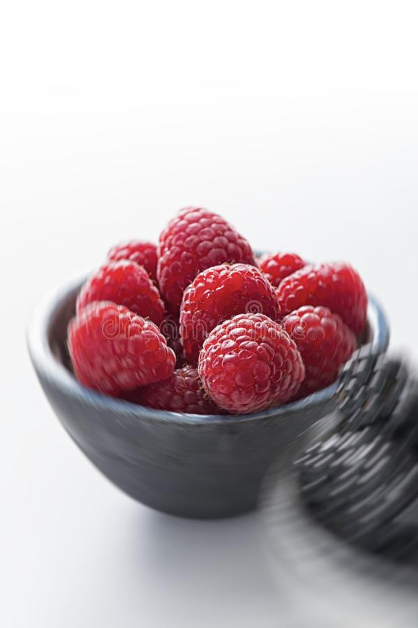 Bowl of raspberries against white background stock photo