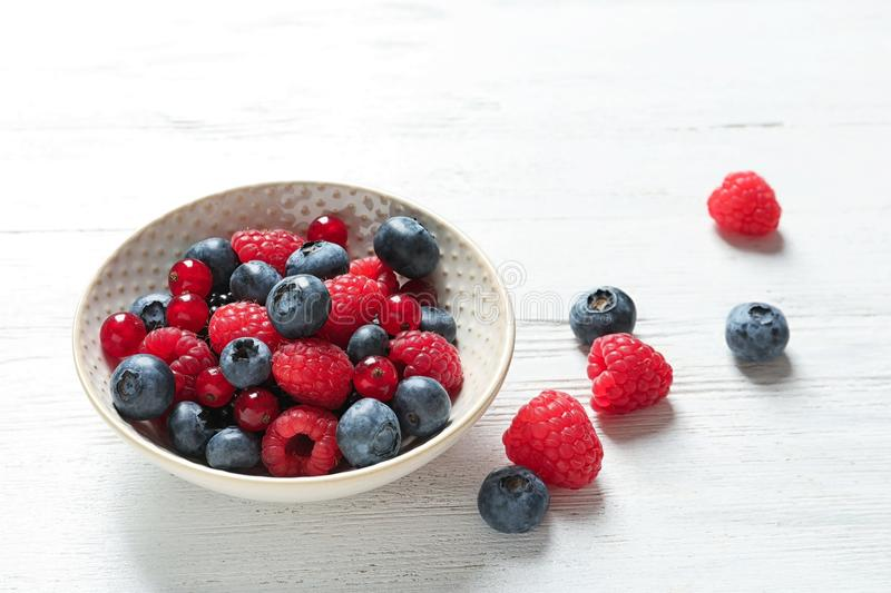Bowl with raspberries, red currant. And blueberries on wooden table royalty free stock images