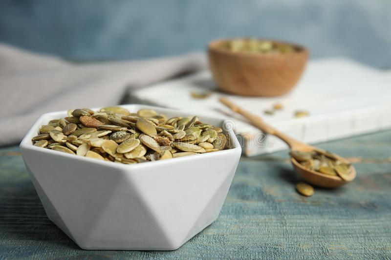 Bowl of raw pumpkin seeds on blue wooden table, closeup. Space for text royalty free stock photography