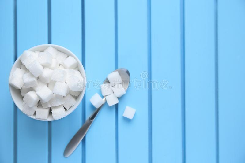 Bowl with refined sugar cubes. On color wooden background, top view stock photo