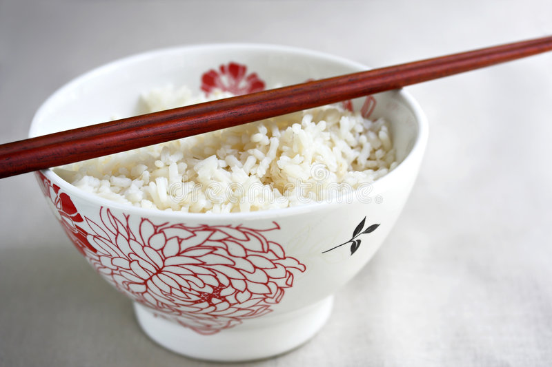 Bowl of rice and chopsticks stock image
