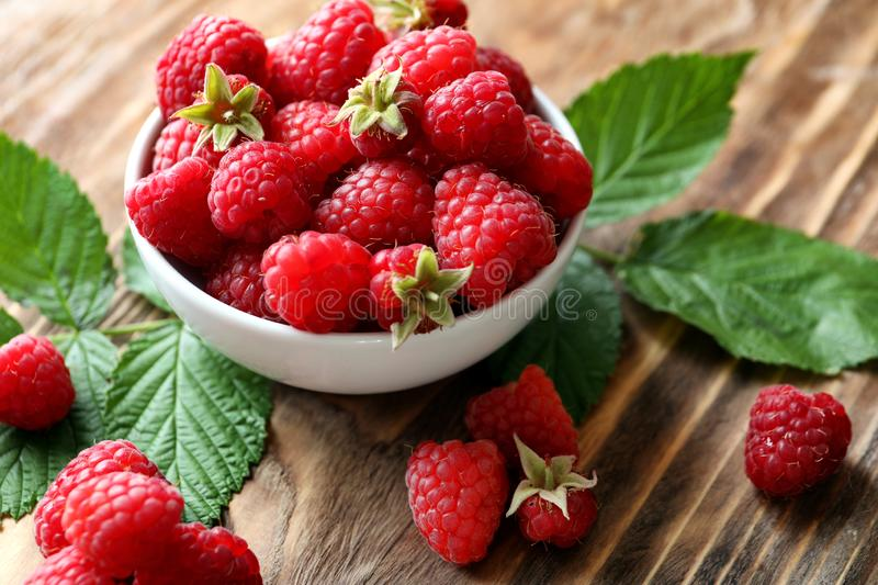 Bowl with ripe aromatic raspberries on wooden background royalty free stock image