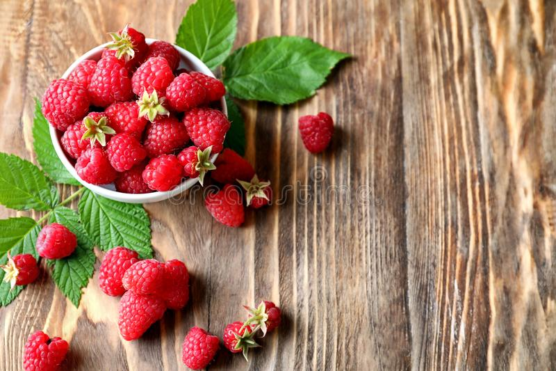 Bowl with ripe aromatic raspberries on wooden background stock image