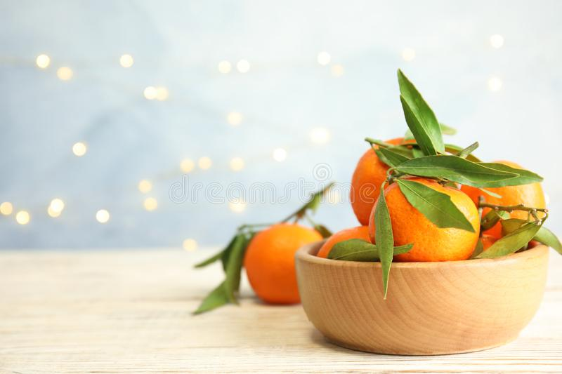 Bowl with ripe tangerines and blurred Christmas lights on background. Space for text royalty free stock photos
