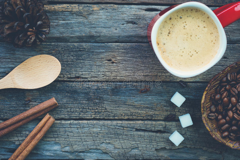 Bowl of roasted coffee beans, red cup of coffee and a spoon with royalty free stock photos