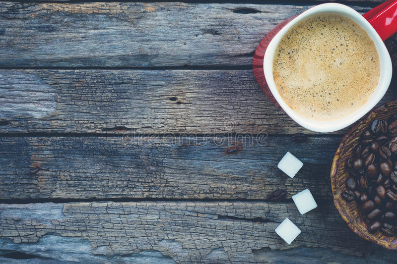 Bowl of roasted coffee beans, red cup of coffee and sugar cubes stock photos