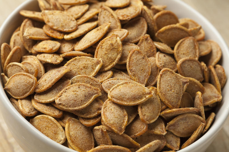 Bowl with roasted pumpkin seeds royalty free stock photography