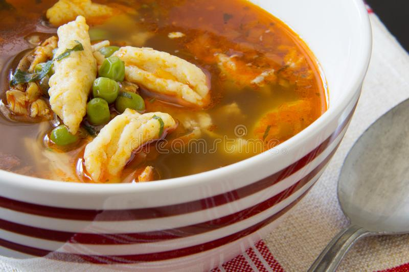 Bowl of Romanian chicken and dumpling soup with peas on antique linen handmade red striped tablecloth with antique spoon. stock photo