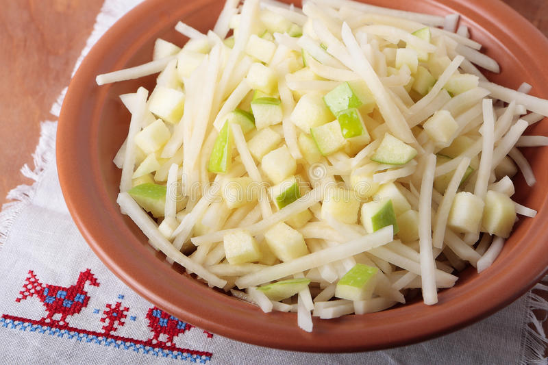 Bowl of salad with apples and black radish. Salad with black radish, apples and honey in a bowl stock image