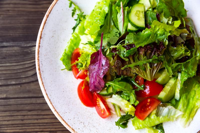 Bowl of salad with vegetables on wooden table stock photography