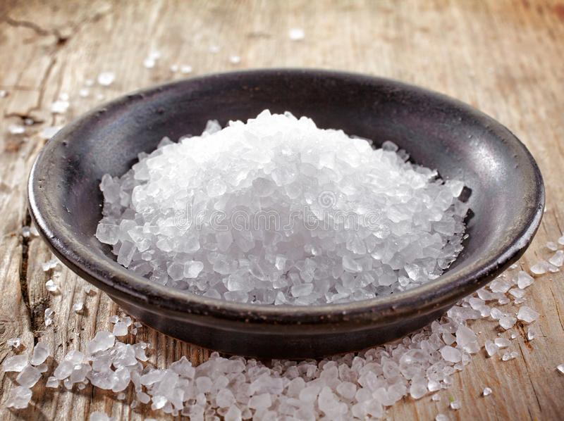 Bowl of sea salt. On wooden table royalty free stock photo