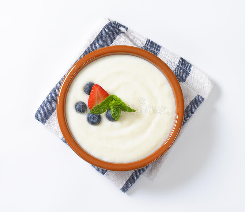 Bowl of semolina pudding with fruit stock images