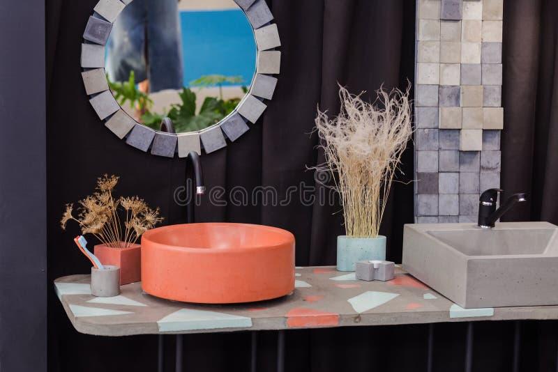 Bowl-shaped concrete sink, orange cement sink, black faucet, wall mirror, original bathroom stock photography