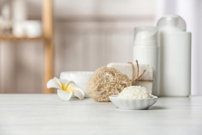 Bowl with Shea butter and other cosmetic products on table in bathroom. Space for text stock photos