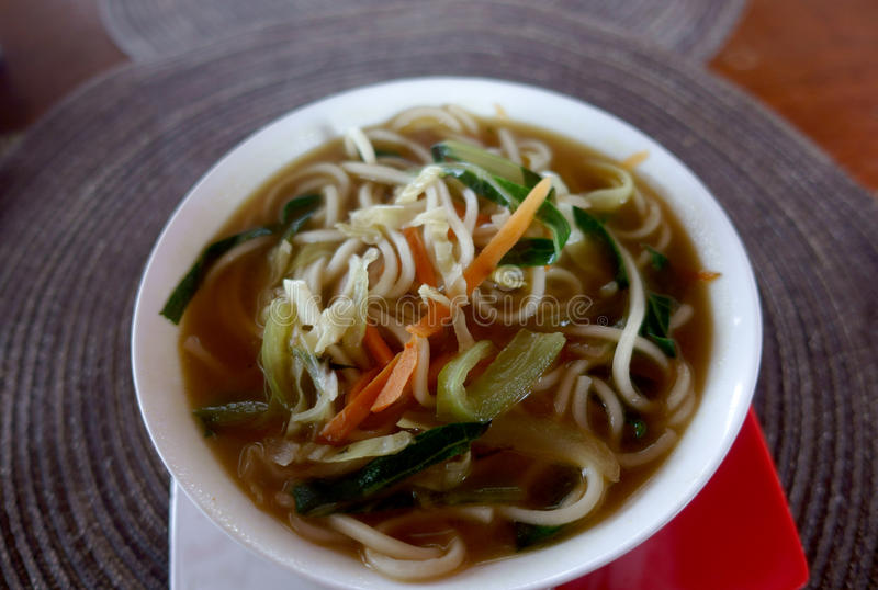 A bowl of soup with noodles and vegetables on a round napkin royalty free stock photography