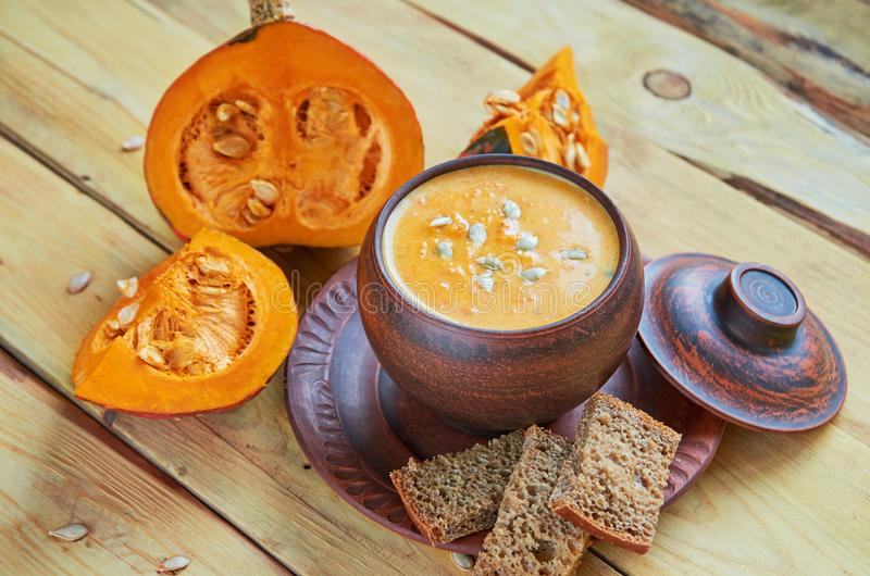 Bowl of spicy pumpkin soup with sliced yellow pumpkins, seeds and bread on the wooden background. Traditional autumn food stock images